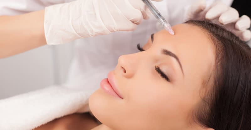 Woman's forehead about to recieve an injection of BOTOX