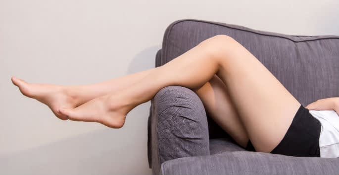 A female pair of legs in black shorts drapped over the arm of a grey sofa