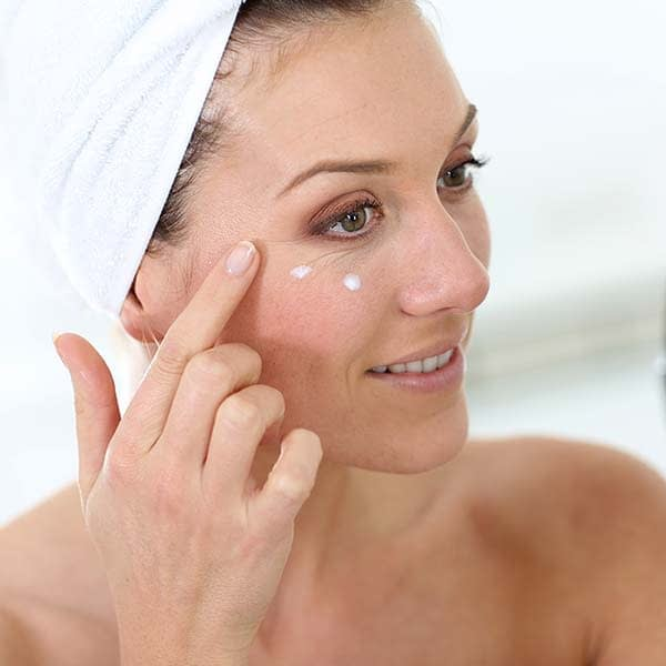Close-up of showered woman with hair in a towel applying eye cream to cheekline
