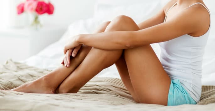 A woman relaxing on her bed in blue shorts with arms around her legs
