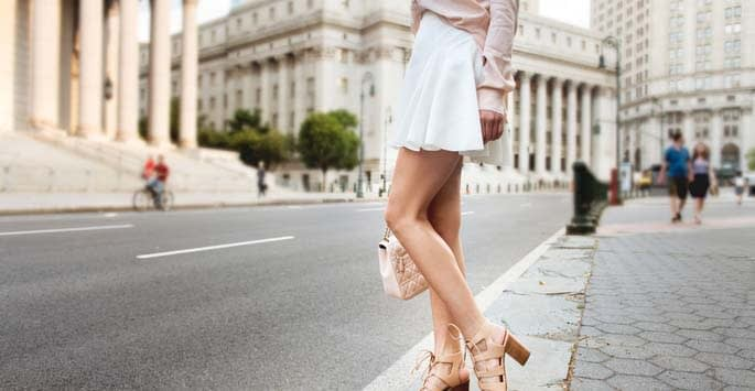 Beautiful legs free of spider veins allow woman to wear short, flowy white skirt to show off her legs while in the city