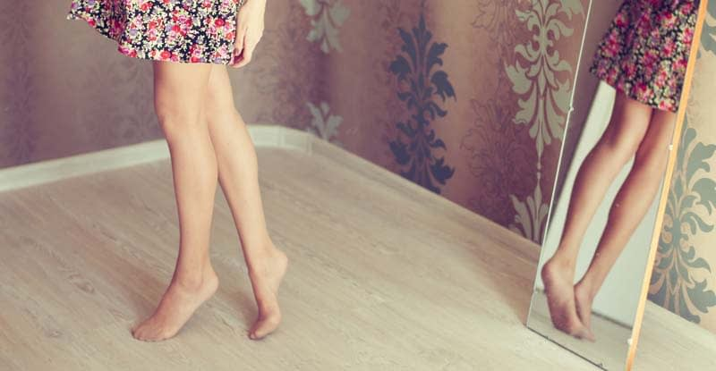 Close up of lady's legs as she admires the back of them in a full-length mirror