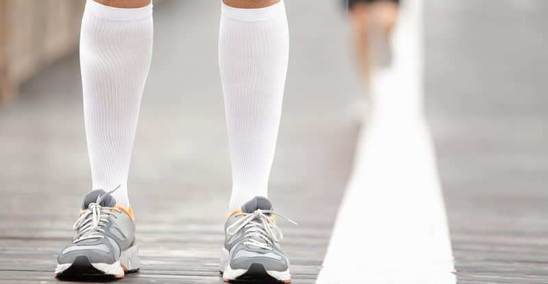 A pair of calves in running shoes wearing compression stockings for vein compression therapy