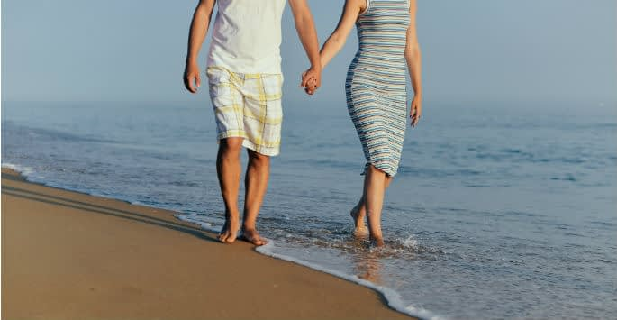 A couple holding hands while walking on the ocean's edge