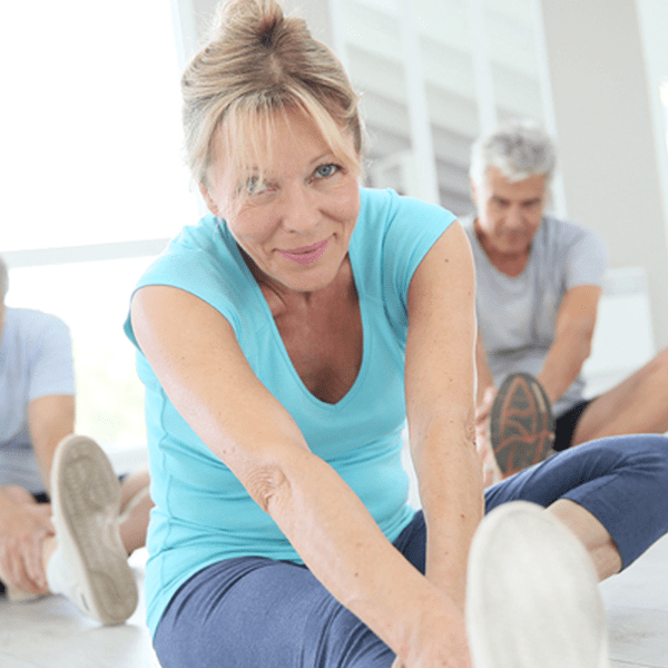 Middle-aged woman stretching legs in exercise class