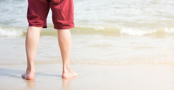 The back of a man's legs in red shorts standing at the edge of the beach