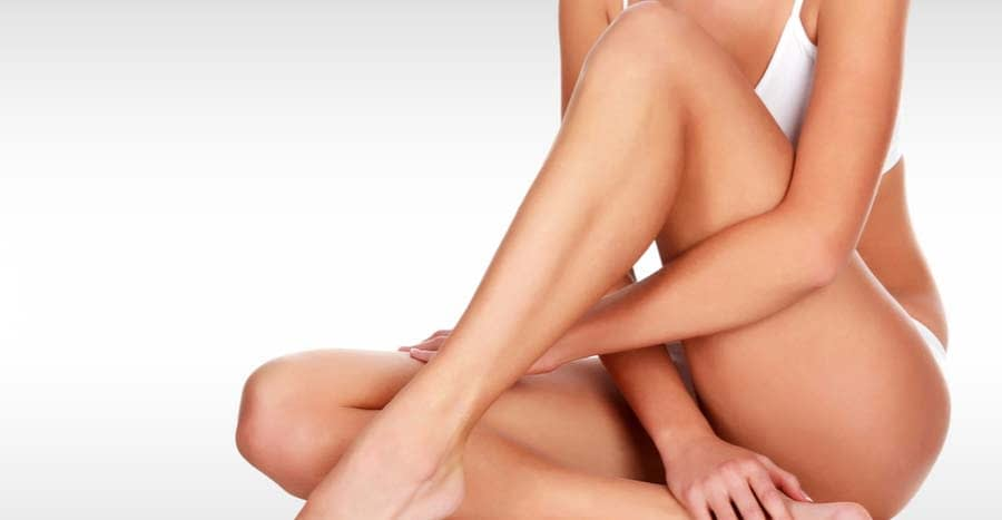The beautiful smooth and tan legs of a woman in her undergarments