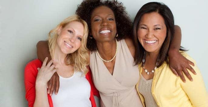 Three female friends smiling and embracing each other
