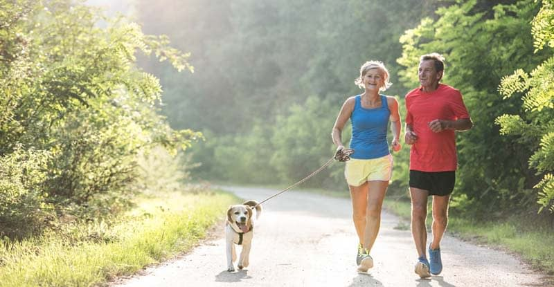 Jogging couple with their dog on a rural road in Crystal Lake, Illinois
