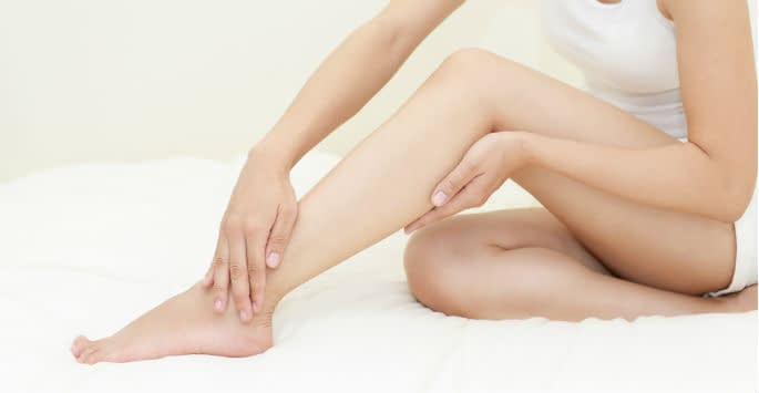 Seated woman rubbing bare legs to reduce inflammation and increase leg blood flow in the veins
