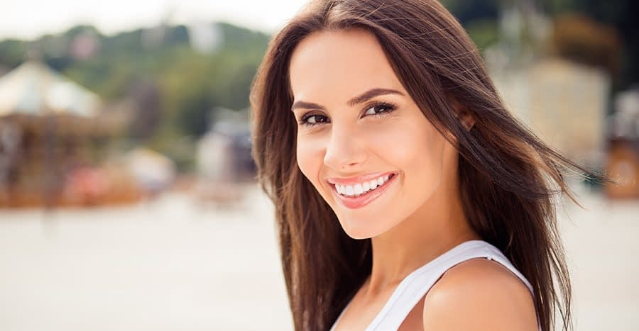 Dark brown, straight-haired brunette with big smile and pretty white teeth looking at you