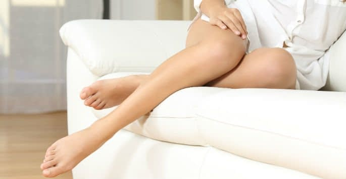A woman wearing a white shirt sitting on a white sofa display her beautiful varicose vein-free legs