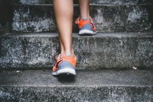 Sneakered feet walking up stone stairs keep legs healthy