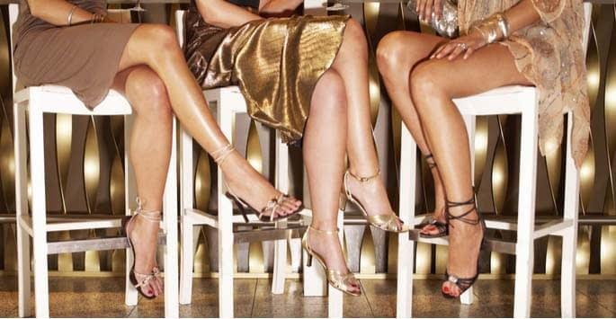 Beautiful legs of women seated in white bar stools at a festive event