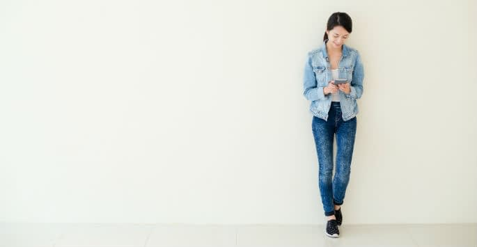 An Asian woman wearing jeans leaning against a wall while viewing smartphone