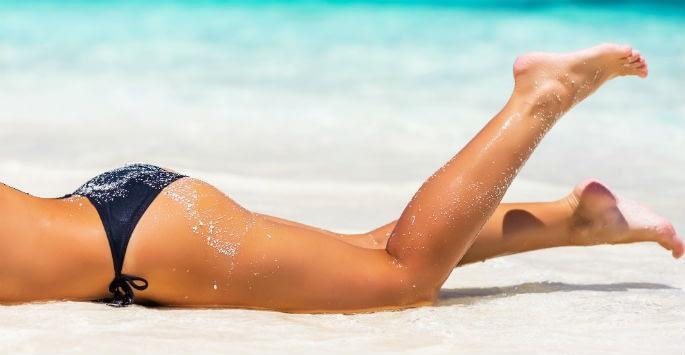 Tanned healthy legs of a woman at the beach in a bikini