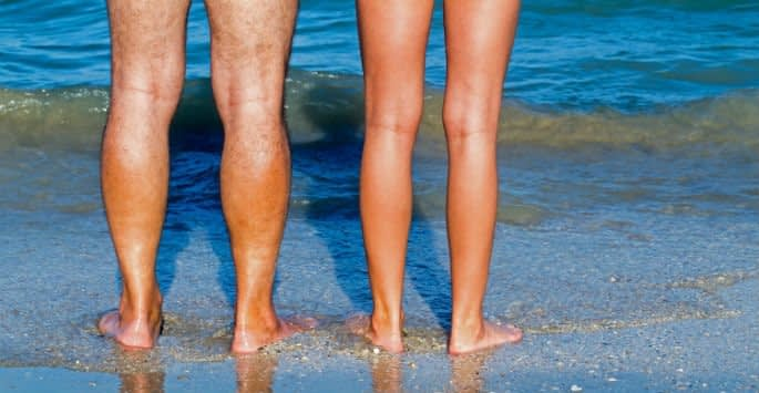 A couple's bare legs standing at the edge of the ocean