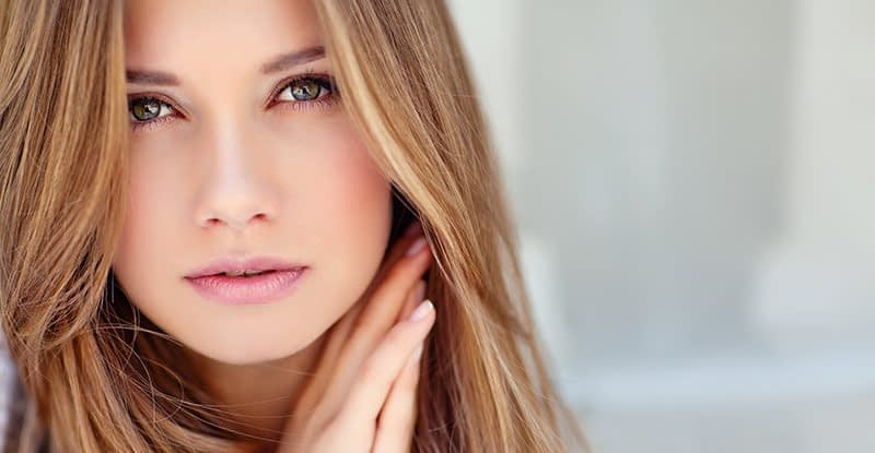 Close-up of pretty woman with straight brown hair and wrinkle-free face