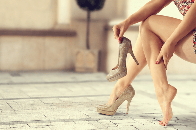 A lady removing one of her beige high-heels and rubbing the back of her calf while seated