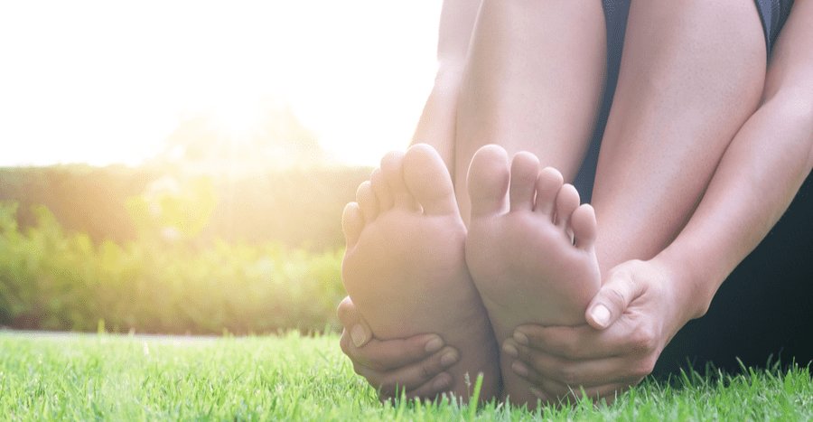 Feet being supported from underneath by hands while seated in grass