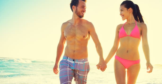 A young couple in swimsuits holding hands while walking on the beach