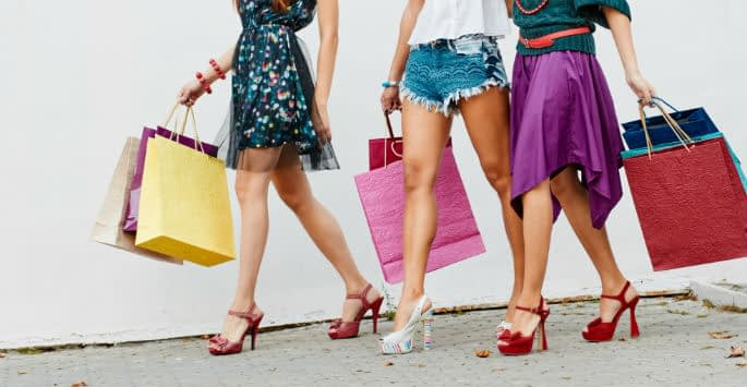 Close-up of 3 women's bare legs in high-heeled sandals carrying colorful shopping bags