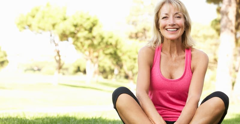 Middle-aged lady doing yoga outdoors