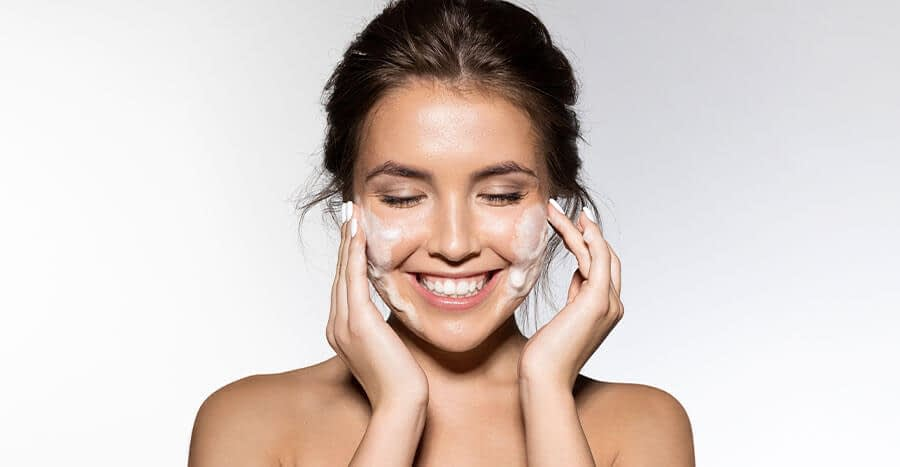 Smiling female with her hair pulled back as she applies facial cleanser to her face