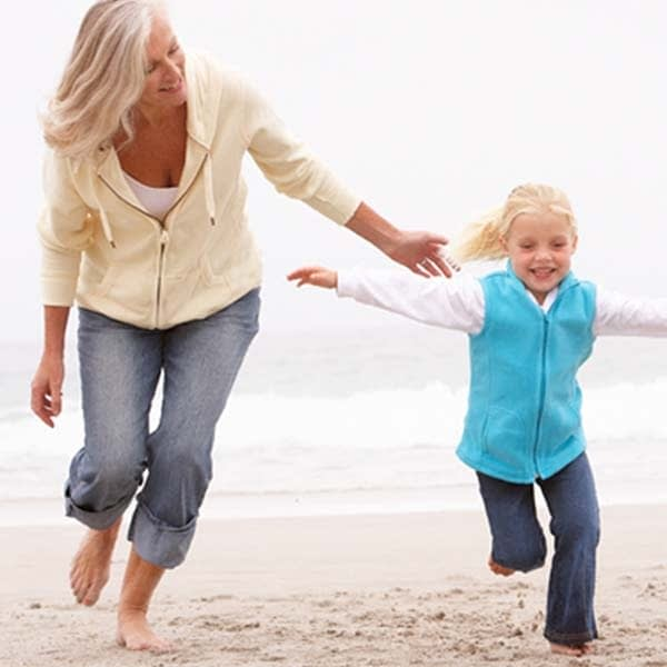 Grandmother in jeans on beach with granddaughter