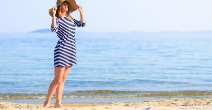 Blonde haired woman in floppy beach hat enjoying the beach