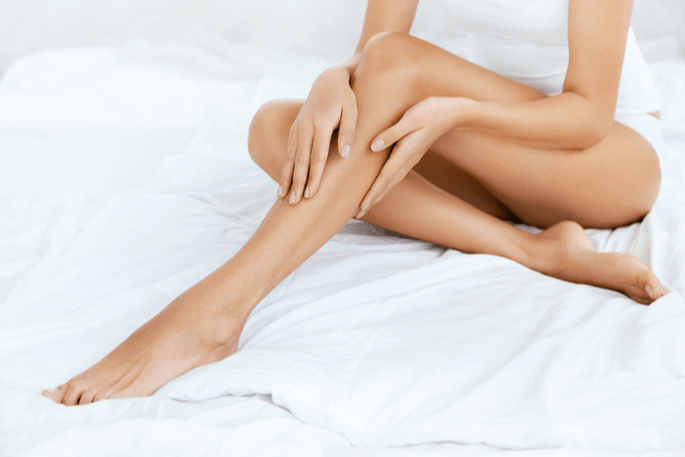 A pair of beautiful legs shown on white bed sheets