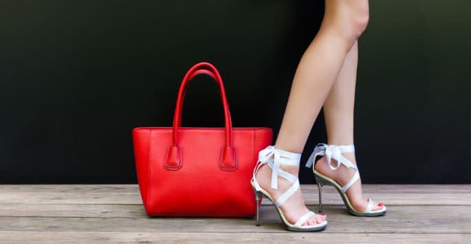 A pair of bare legs in strappy sandals with red purse on the floor nearby