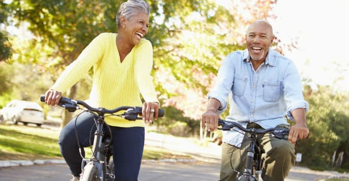 An active older Black couple riding bikes in a residential neighborhood