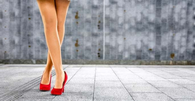 Showing off a beautiful pair of naked legs in red pumps on stone patio