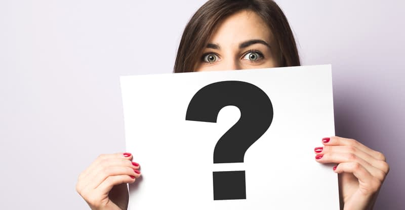 Woman holding sign with question mark for FAQs about veins