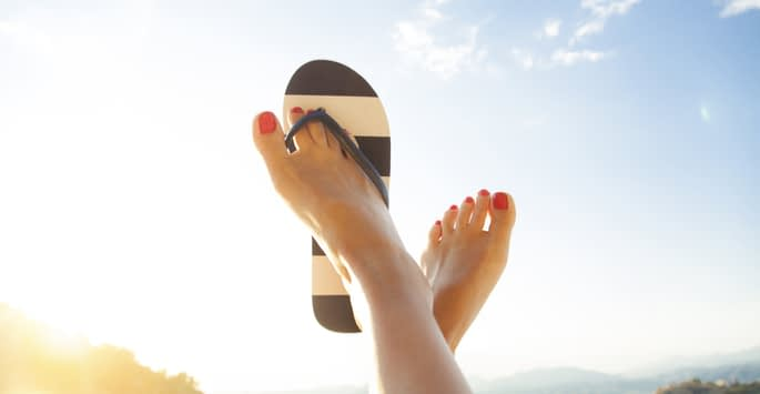 One flip-flop on a pair of raised red-toenailed feet pointed up towards the sky